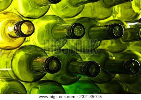 Close Up Stack Of Many Empty Washed Green Glass Wine Bottle Necks, Low Angle Side View