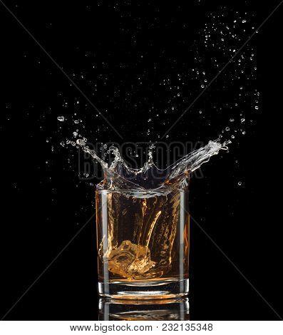Isolated Shot Of Whiskey With Splash On Black Background.