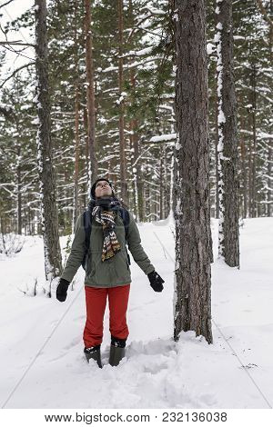 A Nice Smiling Woman Is Standing, Holding Out Her Hands To The Sides And Admiring The Winter, Snow-c