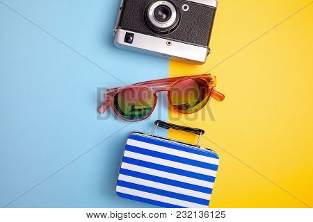Summer Holiday Concept, Travel Concept With Bag, Camera And Glasses On Blue And Yellow Background.