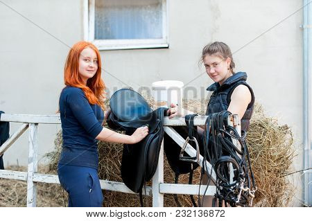 Two Pretty Smiling Teenage Girls Equestrian Clean Black Leather Horse Saddle And Equipment At Stable