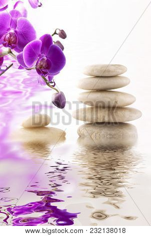 Tower Of Pebbles For Massage And Purple Orchids Reflected In Water