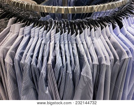 Clothes hang on a shelf . Cloth Hangers with striped Shirts. Men's business clothes