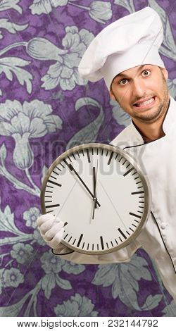 Male Chef Holding Wall Clock On Wallpaper