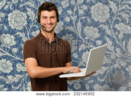 Man With Microphone Holding Laptop Against Wallpaper