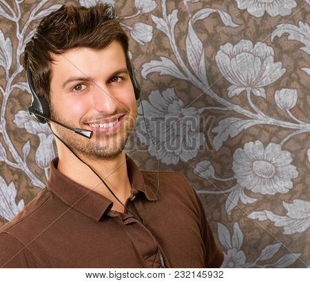 Happy Young Man With Microphone Against Wallpaper