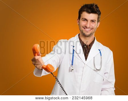 Portrait Of A Doctor Holding Telephone Isolated On Coloured Background