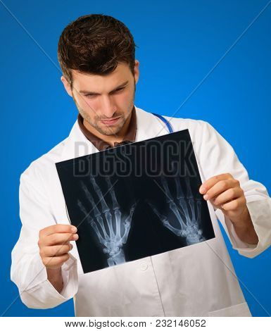Doctor Looking At X-ray On Blue Background