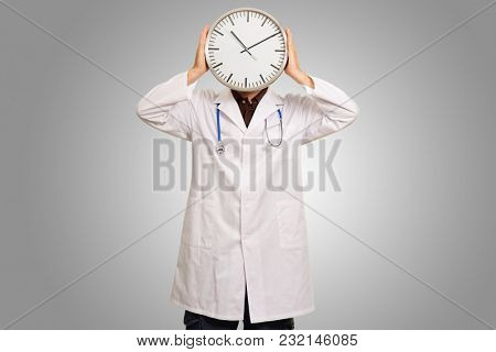Portrait Of Doctor Hiding Face With Clock Isolated On Grey Background