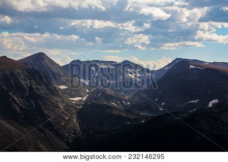 Snow Capped Mountaintops With Lakes, Ponds, Blue Sky, White Cumulus Clouds In Rocky Mountain Nationa