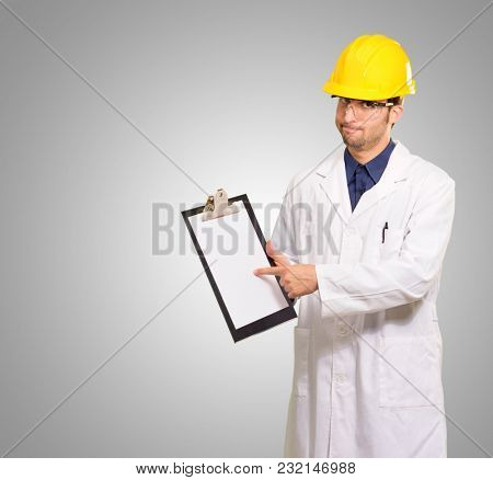 Male Architect Pointing On Clipboard On Grey Background