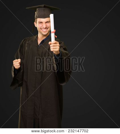 Young Graduation Man Holding Certificate Isolated On Black Background