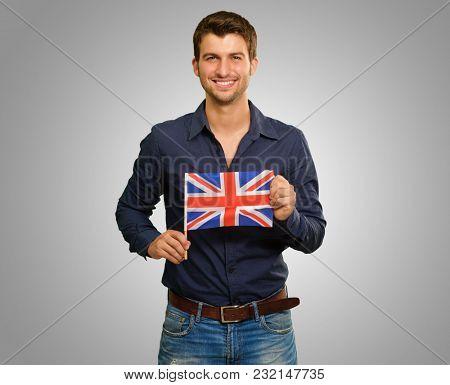 Young Man Holding Flag Of United Kingdom Isolated On Grey Background