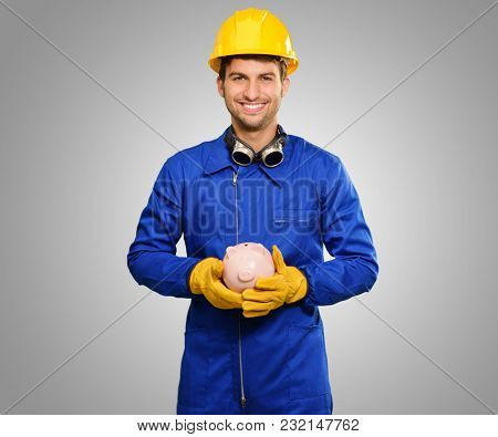 Happy Engineer Holding Piggy Bank Isolated On Grey Background