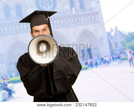 Graduate Man Shouting Into The Megaphone In Front Of University