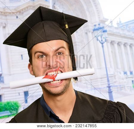 Graduate Man With Certificate In Mouth, Outdoors