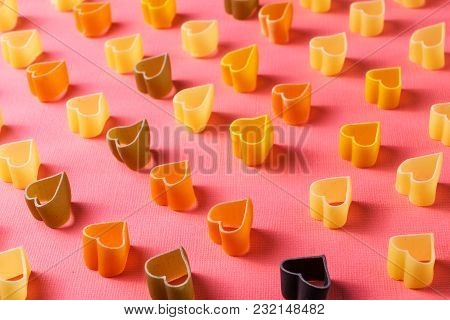 Minimalism style. Repetition concept. View from above on pasta pattern with heart shape, on colored pink background. poster