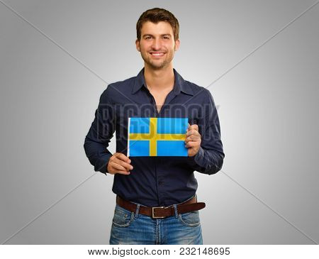 Young Man Holding Flag Of Sweden Isolated On Grey Background