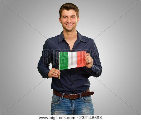 Young Happy Man Holding Irish Flag On Grey Background