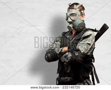 Portrait Of A Soldier With Gas Mask against a concrete background