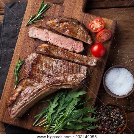 Grilled Cowboy Beef Steak, Herbs And Spices On A Rustic Wooden Background. Top View.