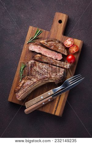 Grilled Cowboy Beef Steak, Herbs And Spices On A Dark Stone Background. Top View.