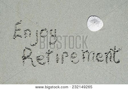 Enjoy Retirement Written In Ocean Beach Sands With Sand Dollar. Conceptual Message Of Retiring, Enjo