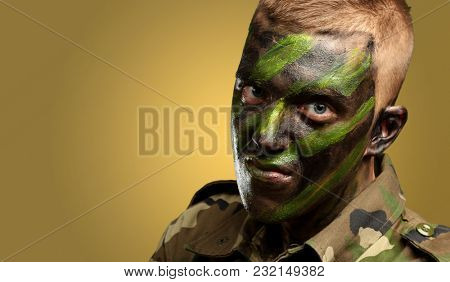 portrait of a soldier with camouflage painting against a yellow background