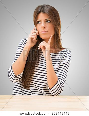Young Woman Talking On Cellphone against a grey background