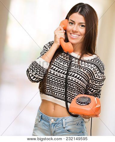 Young Woman Talking On Telephone against an abstract background
