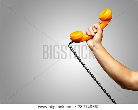 Close Up Of Hand Holding Telephone against a grey background