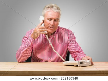 Serious Man Talking On Telephone against a grey background