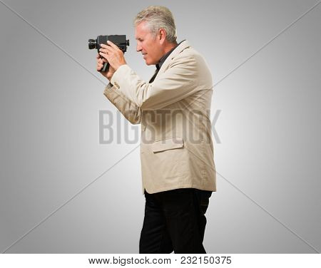 Man Holding Camcorder Side Ways against a grey background