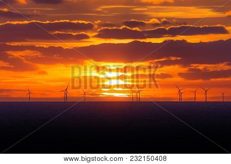 Sunset At Wind Turbines Windmills Offshore Clean Hot Power Farm. Many Energy Stations On Sea Water,