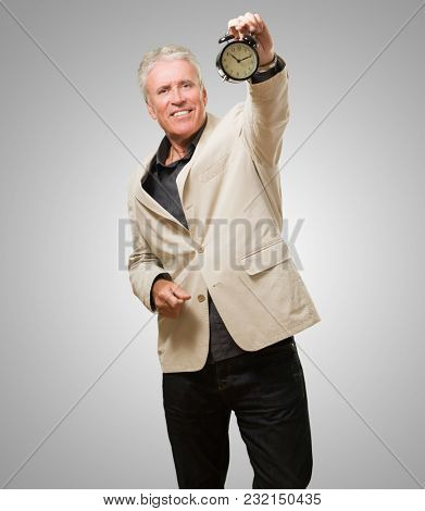 Man Showing Alarm Clock against a grey background