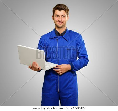 Happy Engineer Holding Laptop  On Grey Background