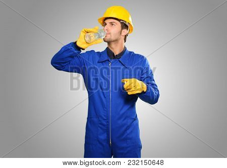 Engineer Drinking Water Isolated On Grey Background