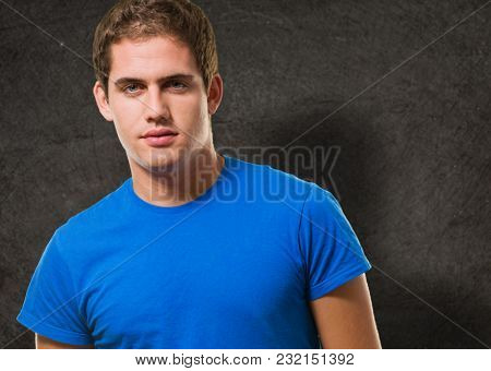 Happy young man posing against a grunge background