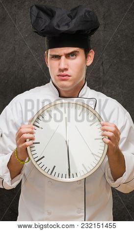 Angry Young Chef Holding Clock against a grunge background