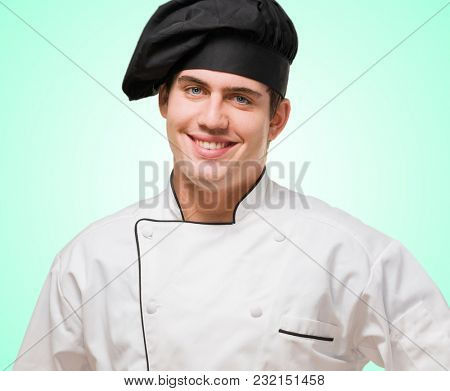 Portrait Of A Young Chef With Hand On Hip against a turquoise background