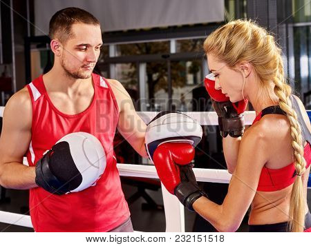 Boxing workout woman in fitness class ring. Sport box exercise two people. Man trainer holding sport mitts in gym. Female box gloves are red backview. Preparation for Championship in boxing.