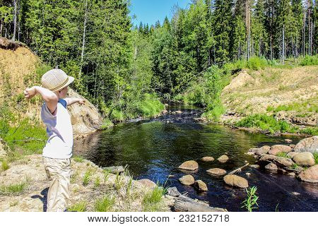 Young Boy Throwing Stones In A River In The Forest