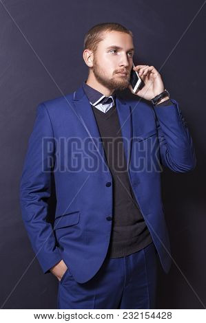 Serious Young Man In A Suit Speaks On The Phone.