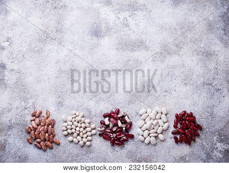 Assortment Of Various Beans On Light Concrete Background. Top View
