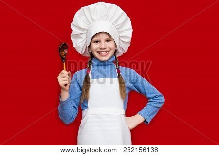 Happy Little Girl In Chef Uniform Holds Spoon Isolated On Red. Kid Chef. Cooking Process Concept