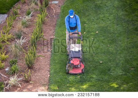 Gardener Mowing The Lawn Facing Camera High Angle View