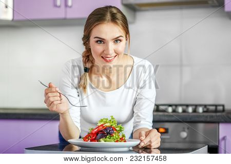 A Young Healthy Girl Eats A Vegetable Salad. Happy Woman At Home. Vegetarian. The Concept Is Healthy