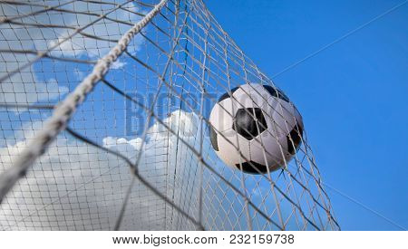 soccer ball in a net and a blue sky