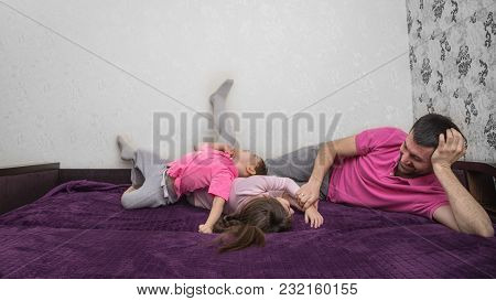 Father And His Two Kids Are Lying On Bed. Family Is Having Fun. Girl And Father Are Lying On One Sid