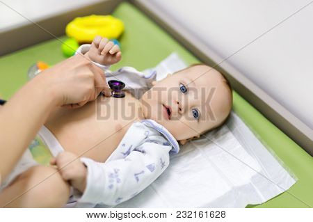 Cute Baby At Doctor's Cabinet. Pediatrician Making Examination Of Child With Stethoscope. Smiling He